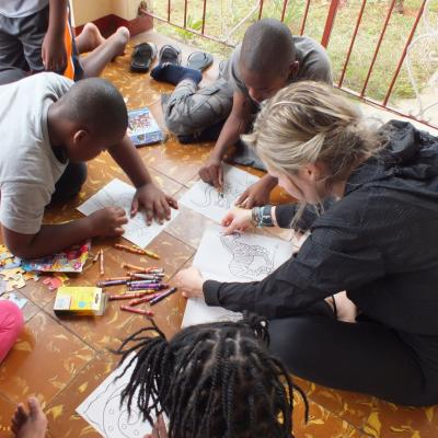 A Projects Abroad volunteer on her Spring Break Project coloring books with the children at her Childcare placement in Jamaica